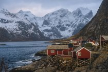 Fishing village buildings on shore with snowcapped mountains — Stock Photo