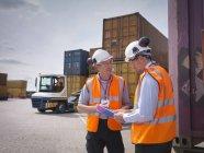 Trabajadores portuarios y contenedores marítimos en puerto - foto de stock