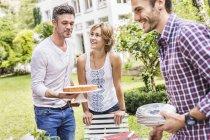 Gruppo di amici che organizzano una festa in giardino, uomo medio adulto che porta la torta — Foto stock