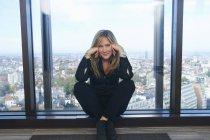 Портрет уверенной деловой женщины, сидящей перед окном офиса с Брюсселем, Бельгия — стоковое фото