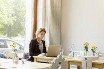 Mujer joven escribiendo en el ordenador portátil en la cafetería - foto de stock