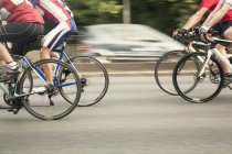 Neck down view of four racing cyclists speeding on urban road in racing cycle race — Stock Photo