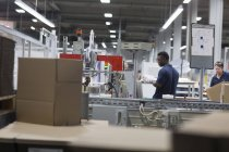 Двоє чоловіків робітники в паперовій упаковці заводу — стокове фото