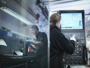 Reflection of male engineer at CNC work station with female engineer — Stock Photo