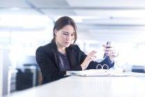 Бізнес-леді за допомогою смартфона в офісі — стокове фото