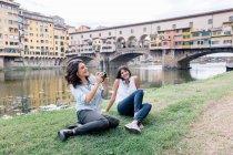 Lesbisches Paar sitzt am Arno Flussufer vor Ponte Vecchio hält Digitalkamera lächelnd, Florenz, Toskana, Italien — Stockfoto