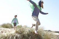 Deux jeunes garçons, vêtus d'une robe chic, jouant sur la plage — Photo de stock