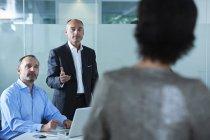 Бизнесмены и женщины спорят за столом в зале заседаний — стоковое фото