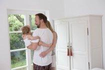 Батько проведення baby дочка, жінка з руки навколо людини — стокове фото
