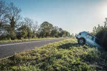 Crashed car sticking out of hedge on rural roadside — Stock Photo
