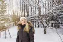 Mi femme adulte devant les arbres couvertes de neige à la recherche de suite souriant — Photo de stock