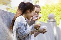 Дві молоді жінки притулившись парк стіна, сміючись і пити каву винос — стокове фото