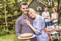 Gruppo di amici alla festa in giardino, giovane che tiene la torta — Foto stock