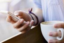 Cortada a vista da jovem mulher mãos segurando uma xícara de café usando smartphone — Fotografia de Stock