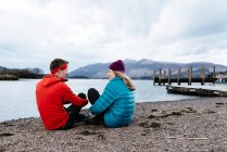 Young couple hiking, sitting by waters edge, Derwent Water, Keswick, Lake District, Cumbria, United Kingdom — Stock Photo