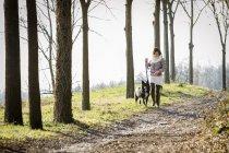 Середине взрослая женщина, идя своей собакой на путь грязи — стоковое фото