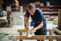 Young male carpenter sanding wood in workshop — Stock Photo