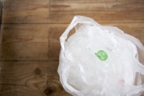Recyclable plastic shopping bags on wooden floor — Stock Photo