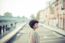 Giovane donna guardando oltre le spalle in città — Foto stock