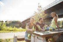 Tre giovani amici che bevono birra sulla panchina da picnic lungo il fiume — Foto stock