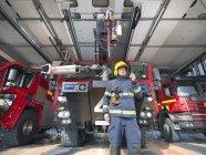 Пожарный использует рацию перед пожарными машинами в пожарной части аэропорта — стоковое фото