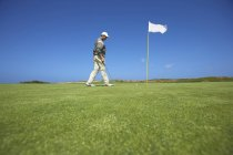 Low angle full length side view of golfer walking to golf flag, looking down — Stock Photo