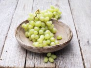 Grapes in wooden bowl on rustic table — Stock Photo