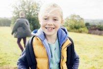 Menina vestindo bodywarmer e sorrindo — Fotografia de Stock