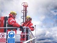 Работники оффшорных ветропарков обсуждают причал на море — стоковое фото