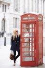 Parejas jóvenes en la cabina del teléfono rojo, Londres, Inglaterra, Reino Unido - foto de stock