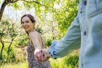 Молодая женщина ведет молодого человека через лес, держа за руку — стоковое фото