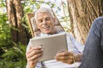 Mature man using digital tablet on hammock — Stock Photo
