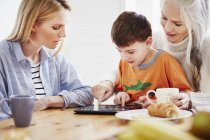 Familia de tres generaciones usando tableta digital - foto de stock