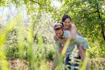 Вид сквозь листву молодого человека, дающего молодой женщине свинью — стоковое фото