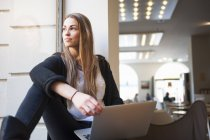 Young woman looking out of cafe window whilst using laptop — Stock Photo