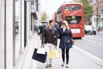 Молода пара з сумками гуляють, Лондон, Великобританія — стокове фото