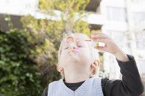 Мальчик пускает пузырьки в сад — стоковое фото