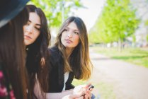 Three young female friends talking in park — Stock Photo