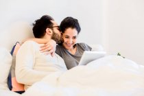 Romantic young couple sitting up in bed using digital tablet — Stock Photo