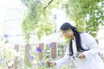 Young female scientist with digital tablet outside laboratory selecting specimen plants — Stock Photo