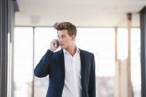 Молодой предприниматель, с использованием смартфона в офисе — стоковое фото