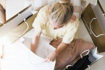 Вид сверху молодой женщины на кровать в окружении сумки — стоковое фото