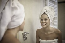 Young woman wearing towel on head looking at reflection in mirror — Stock Photo