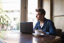 Молодий учень, сидячи в кафе таблиці за допомогою ноутбука і дивлячись з вікна — стокове фото