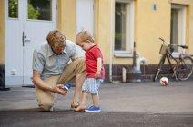 Padre dando hijo pequeño una mano a poner en entrenador en el jardín - foto de stock