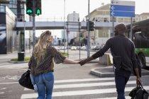 Vista posteriore di camminare donna caucasica e l'uomo etnicità africana in strada, coppia innamorata che trasporta il bagaglio e si tiene per mano, pedoni attraversando la strada — Foto stock