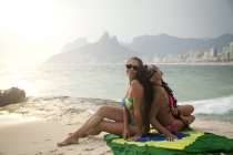 Портрет двух молодых женщин, сидя на бразильского флага, Ипанема, Рио-де-Жанейро, Бразилия — стоковое фото