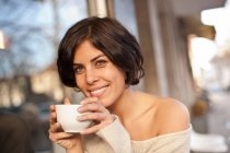 Portrait of woman outside cafe drinking coffee — Stock Photo