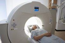 Hombre maduro entrando en el escáner de TC en interiores - foto de stock