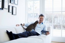 Man relaxing on sofa using digital tablet with cat — Stock Photo